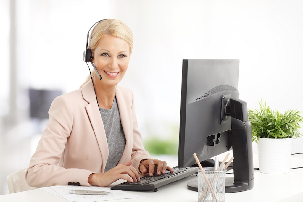 Portrait of smiling business customer service woman smiling while sitting at office in front of computer and working.